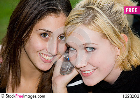 Friends on Cell Phone together (Beautiful Young Blonde and Brune Stock Photo