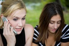 Friends On Cell Phone Together (Beautiful Young Blonde And Brune Royalty Free Stock Photography