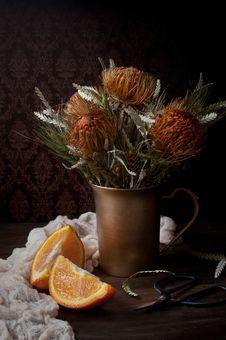 Free Orange Flowers In Brown Vase Beside Sliced Orange Fruit Stock Photos - 132036993