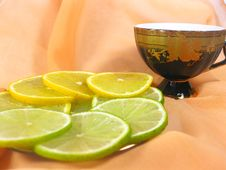 Lemon And Lime With A Cup Of Tea And A Pink Backgr Royalty Free Stock Photography