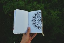 Free Person Holding Open Book With Floral Drawing Stock Photography - 132219412