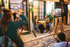 Free Two Man And Woman Taking Photo Of Two Women Sitting And Talking Beside Round Table Beside Road With Menu Board Stock Images - 132385884