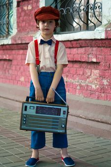 Free Photo Of Boy Holding Radio And Standing Beside Of Red House Stock Photo - 132386040