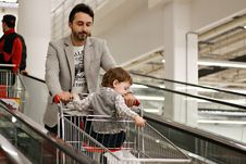Free Man Pushing Shoppers Cart With Baby Sitting Inside Royalty Free Stock Photo - 132386095