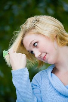 Beautiful Yong Blonde Girl With Blue Eyes Combing Her Hair Stock Photos