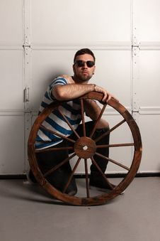 Free Man Kneeling Behind Brown Wooden Carriage Wheel Royalty Free Stock Photography - 133489347