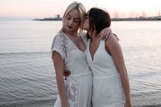 Free Woman Kissing Woman While Standing Near Body Of Water Stock Photos - 133489683