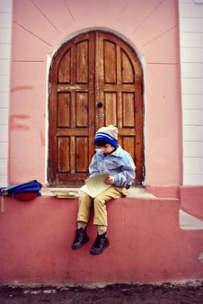 Free Boy Sitting On Stairs Holding Book Stock Images - 133489714