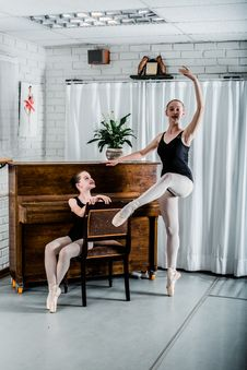 Free Woman Dancing Ballet Beside Girl Sitting On Chair Stock Image - 133728881
