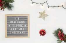 Free It S Beginning To Look A Lot Like Christmas Board Decor Beside Star And Red Bauble Flatlay Photography Royalty Free Stock Photography - 133729097