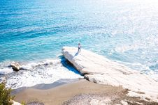 Free Person Standing On White Boulder Near Body Of Water Stock Image - 133792061
