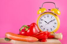 Free Fresh Vegetables On A Wooden Kitchen Board And Retro Clock Isolated On Pink Royalty Free Stock Image - 133895686