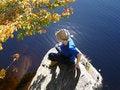 Free Girl Sits Ashore On Large Stone Stock Photography - 1347442