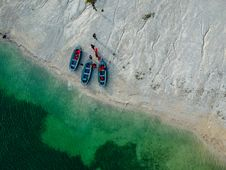 Free People And Three Blue Boats On Beach With Green Water Aerial Photography Royalty Free Stock Photo - 134071875