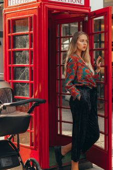 Free Woman Wearing Red And Green Floral Blouse In A Phone Booth Royalty Free Stock Image - 134167916
