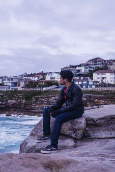 Free Man Sitting On Rock Near In Front Of Ocean Water Royalty Free Stock Photo - 134421165