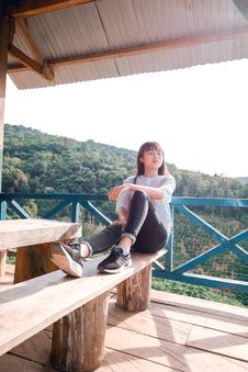 Free Woman In Casual Wear Sitting On Wooden Bench Stock Images - 134421464