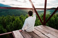 Free Man Sitting On Wooden Surface Looking At Trees Stock Photo - 134421490