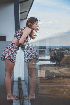 Free Photo Of Woman Leaning Against Glass Balcony Stock Photo - 134472810