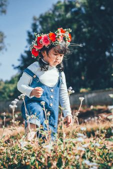Free Girl In Blue Denim Dungaree With Red Flowers On Head Walking On Flower Field Royalty Free Stock Photo - 134722645