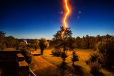 Free Lightning Strikes Tree In Front Of House During Nighttime Stock Photo - 134821700