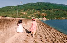 Free Two Girls Walking Near Body Of Water Royalty Free Stock Photography - 134952877