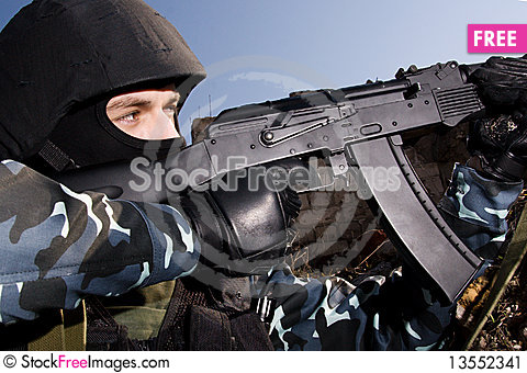 Soldier shooting with rifle from the hideout Stock Photo