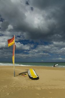 Beach With Life Saving Flag And Rescue Board Royalty Free Stock Image