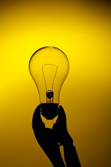 Free A Light Bulb Held In A Grip On A Yellow Gl Stock Photo - 13559330