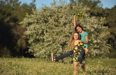 Free Two Beautiful Young Women Piggy-backing In Meadow Royalty Free Stock Images - 13567309