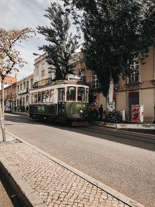 Free Green Tram Near Brown Building Stock Image - 135770911