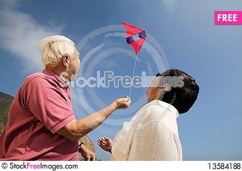 Couple flying kite outdoors Stock Photo