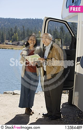 Senior couple looking at map outside RV Stock Photo