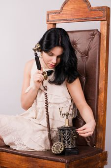 Cheerful Woman Speaks By Ancient Phone Stock Photo