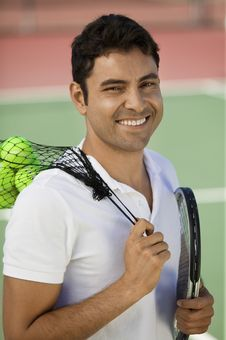 Man On Tennis Court With Tennis Balls And Racket Royalty Free Stock Photos