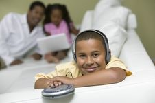 Boy Listening To Music, Father And Sister On Sofa Royalty Free Stock Image