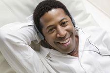 Man Lying On Sofa Listening To Music Stock Photo