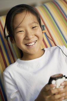 Girl Sitting On Sofa Listening To MP3 Player Royalty Free Stock Image