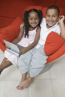 Free Brother And Sister In Chair With DVD Player Stock Image - 13584361