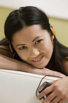 Free Young Woman Lying On Sofa Listening To Music Royalty Free Stock Image - 13584376