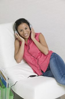 Free Woman Reclining On Chair Listening To Music Royalty Free Stock Photos - 13584398