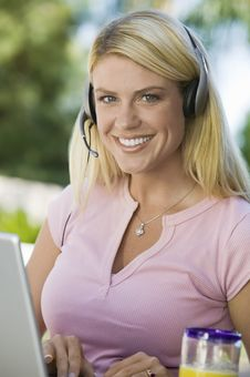Free Woman Using Laptop And Headset Stock Image - 13584411