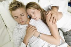 Young Couple Lying On Sofa Together Stock Photo