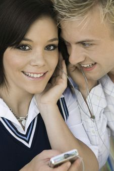Young Couple Sharing Headphones Listening To MP3 Stock Images