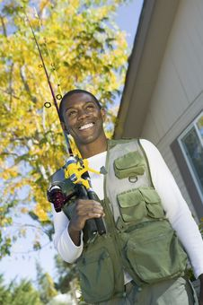 Free Man Holding Fishing Rod In Font Of House Royalty Free Stock Image - 13584746