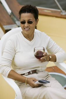 Free Woman Relaxing On Yacht, Holding Glass Of Wine Stock Image - 13584831