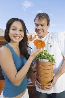 Free Couple Holding Flower Pots In Outdoors Garden Stock Photography - 13585122