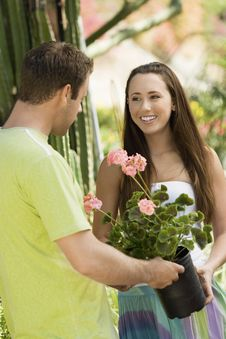Free Young Couple Choosing Potted Flowers Royalty Free Stock Photography - 13585137