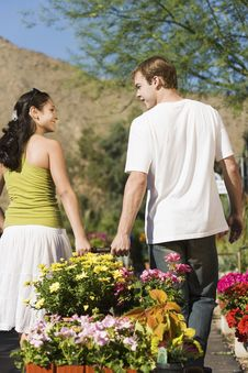 Free Young Couple Pulling Cart With Potted Flowers Stock Photo - 13585140