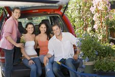 Two Young Couples Sitting In Open Car Trunk Stock Photography